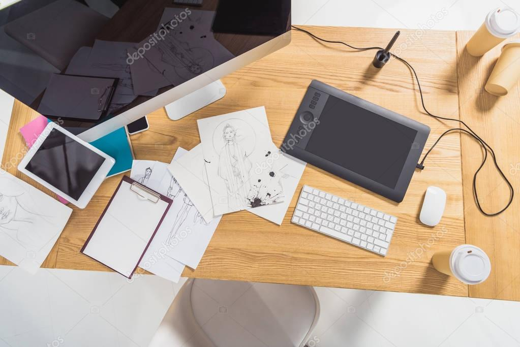 Work place of designer with illustrations and computer