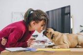 Fotografia Bella signora del pug di baciare mentre si lavora su illustrazioni in ufficio a casa