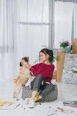Fotografia Bella signora che gioca con il cane sul pavimento del Ministero degli interni