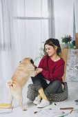 Fotografia Giovane donna che abbraccia sveglio il cane piano tra gli schizzi