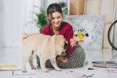 Fotografia Bella signora che gioca con il cucciolo del pug sul pavimento
