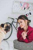 Fotografia Artista di giovane donna guardando il cane del pug