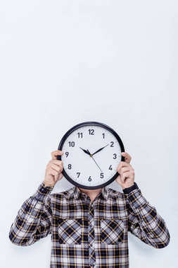 Clock in male hands over his face  isolated on white