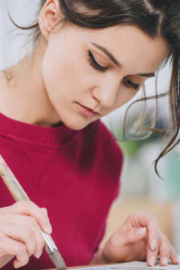 Attractive young girl drawing with large brush