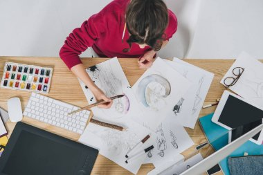Attractive young girl drawing by table with computer