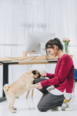 Young woman feeding dog by workspace table