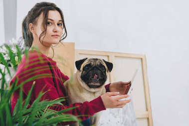 Attractive young girl using tablet and holding dog at home