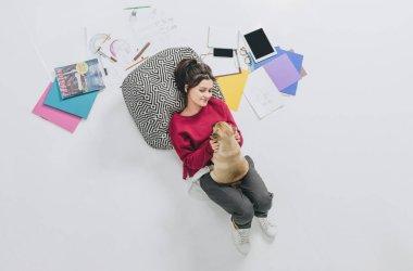 Pretty lady cuddling pug on floor among sketches
