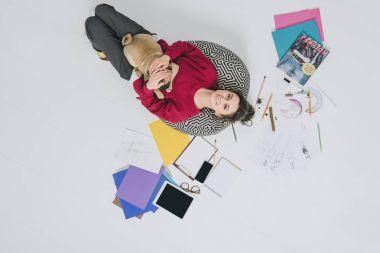 Attractive young girl cuddling pug dog among sketches on floor