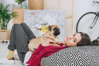 Pretty lady playing with pug puppy on large cushion
