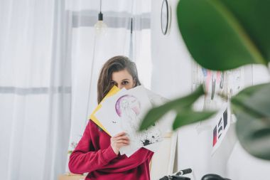 Female designer holding sketches in front of her face