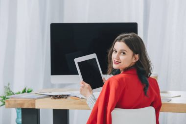 Pretty lady holding tablet by working table with computer
