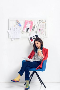 Pretty lady working on tablet and holding coffee cup in light studio