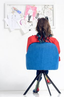 Rear view of woman looking at mood board