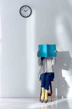 Attractive young girl reading and holding book over her face