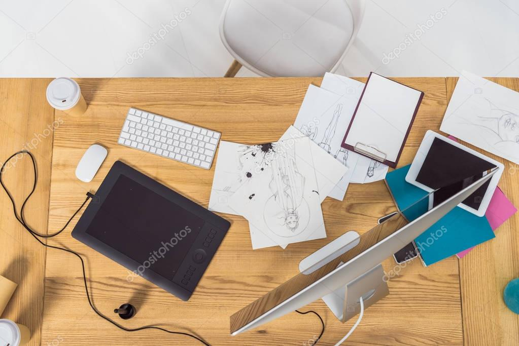 Top view of designer workplace with fashion illustrations and computer