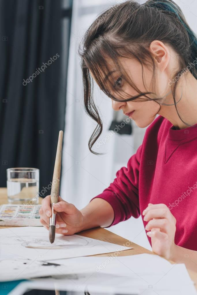 Female designer drawing with large brush