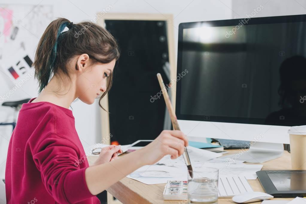 Young woman drawing on table with computer