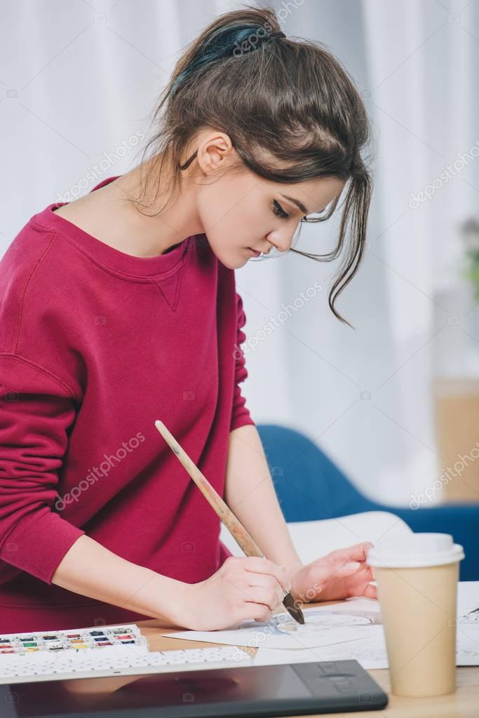 Pretty lady drawing on table at home office