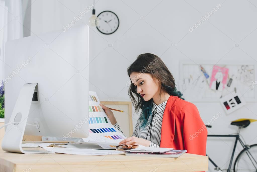 Female designer working with palette by working table with computer