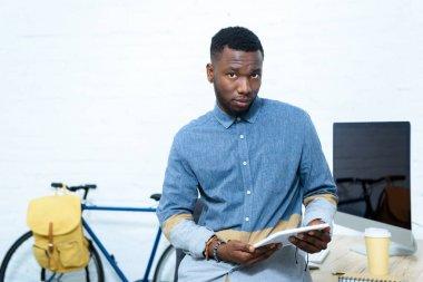 Young man using digital tablet and looking at camera