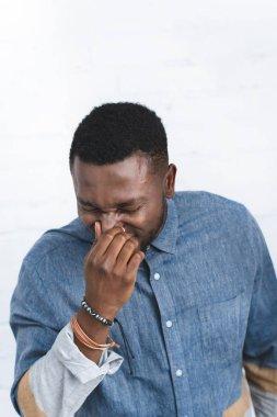 Handsome african american man sneezing