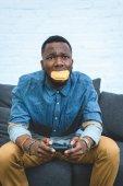 schöner afrikanisch-amerikanischer Mann spielt mit Steuerknüppel und hält Hamburger im Mund