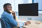 Afrikanisch-amerikanischer Mann arbeitet am Computer und isst Hamburger