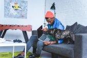 Young man showing laptop screen to cute French bulldog