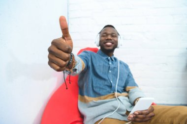 Young man showing thumb up with smartphone and listening to music in headphones