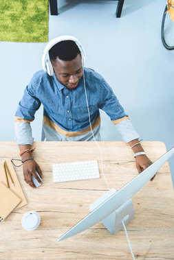 African american man working by computer table