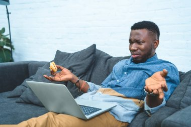 Confused african american man working on laptop while sitting on sofa and eating hamburger