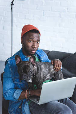 Handsome african american man working on laptop and hugging Frenchie dog