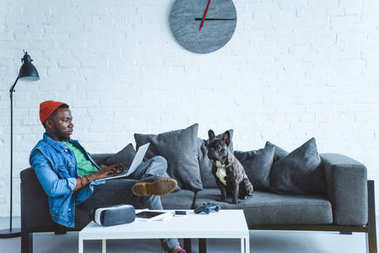 African american man working on laptop while sitting on sofa with bulldog and digital gadgets on table