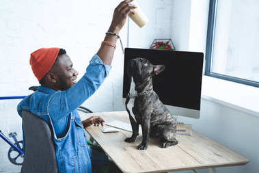 Handsome african american man playing with dog on computer table