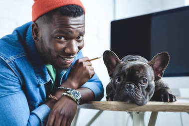 Handsome african american man with Frenchie dog by computer screen