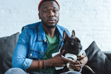 Young man wearing headphones on Frenchie dog