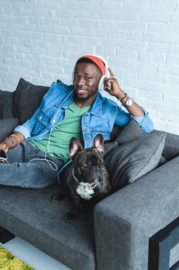 Frenchie dog on sofa sitting by African american man in headphones listening to music