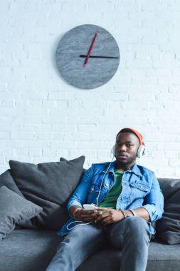 African american man in headphones listening to music on phone