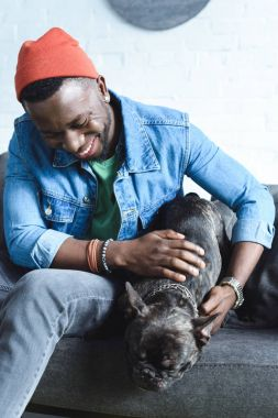 Handsome african american man playing with black Frenchie on sofa