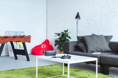 Digital gadgets on table in modern room with sofa