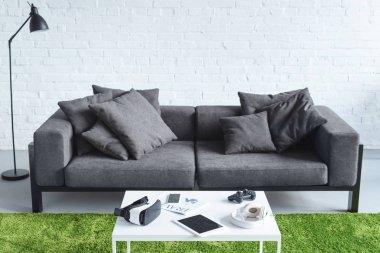 Digital gadgets in cozy interior with modern grey sofa stock vector