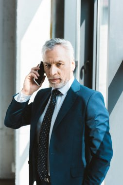 serious senior businessman talking by smartphone and looking at camera