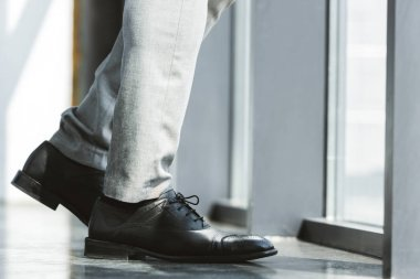 cropped shot of stylish businessman standing in fashionable leather shoes and pants