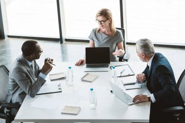 high angle view of businesswoman showing laptop with blank screen and looking at male colleagues during meeting