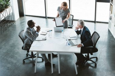 high angle view of businesswoman showing blank clipboard to multiethnic businessmen at meeting