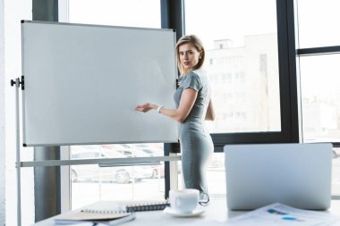 beautiful businesswoman pointing at blank whiteboard and looking at camera