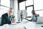 Fotografie multiethnische Geschäftskollegen blicken in die Kamera, während sie sich bei einem Geschäftstreffen unterhalten
