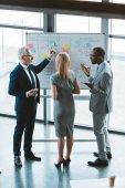 Fotografie zadní pohled na profesionální mnohonárodnostní kolegů pojednávající o obchodní grafy a grafy na tabuli