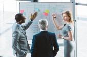 zadní pohled na profesionální mnohonárodnostní obchodních lidí diskutovat a grafy na tabuli